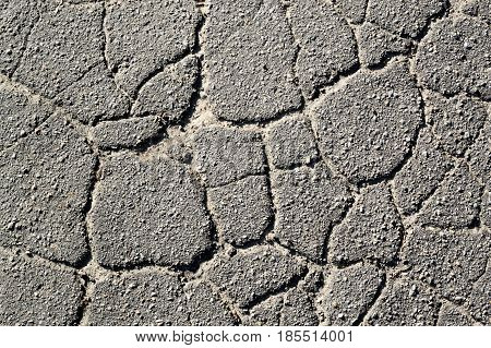 Texture of old cracked asphalt in the daytime. Background