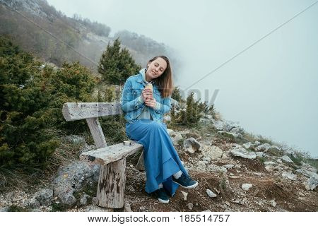 Smiling Woman Sitting On Wooden Bench And Drinking Hot Tea From A Thermos In Autumn Forest.