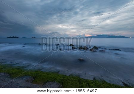 A moody morning sky over Nha Trang bay Vietnam just before sunrise with moss covered rocks in the foreground.