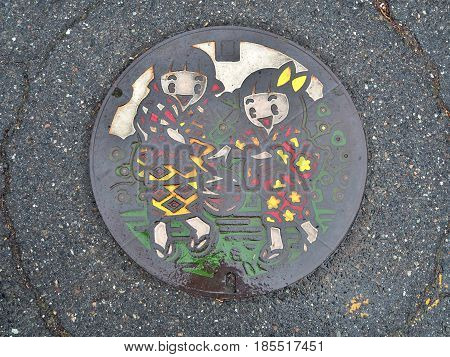 Nagano, Japan - February 20, 2017: A manhole cover of Matsumoto city, Nagano Prefecture, Japan. Two girls in Kimono play Temari ball engraved on a manhole cover. Temari ball is folkcraft ball.