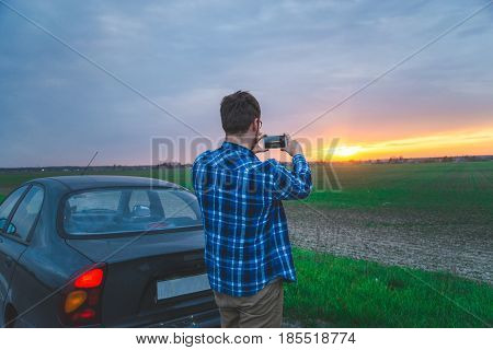 man taking picture of sunrice car travel