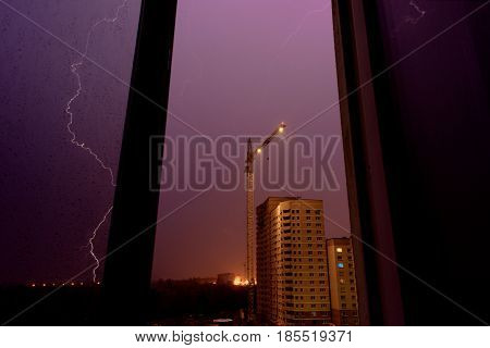Thunderstorm, lightning stroke over the construction site, view from the window