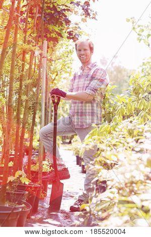 Full-length portrait of happy man holding spade at garden