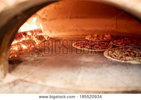 food, italian kitchen and cooking concept - pizza baking in oven at pizzeria