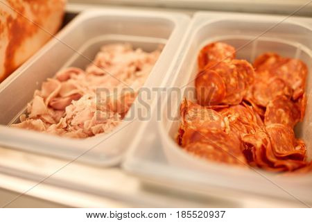 cooking, storage and food concept - containers with ham and salami at restaurant kitchen
