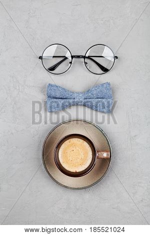 Happy Fathers Day background with morning coffee mug glasses and bowtie on stone gray table top view in flat lay style.