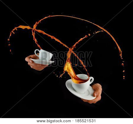 Man hands holding porcelain cups with splashing liquid of coffee or tea, isolated on black background. Hot drink with splashes, beverages and refreshment.