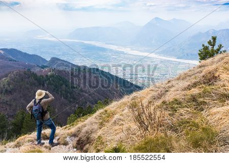 Hiker looking from Monte Chiampon to plain of Friuli-Venezia Giulia in Italy in spring
