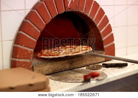 food, italian kitchen and cooking concept - peel taking baked pizza out of oven at pizzeria