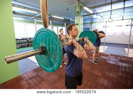 fitness, sport, training, exercising and people concept - group of men with barbells doing standing shoulder press in gym