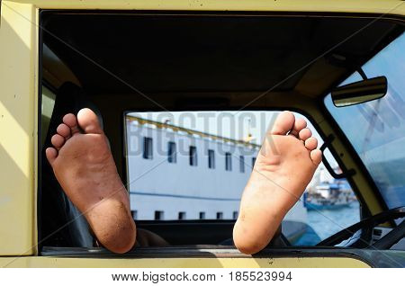 Feet of the Indonesian driver resting in his car during several days' expectation of the ferry to the next island