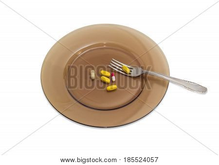 Several yellow tablets of the multivitamins and different dietary supplements in the form of capsules on the big dark glass dish with the stainless steel fork on a light background