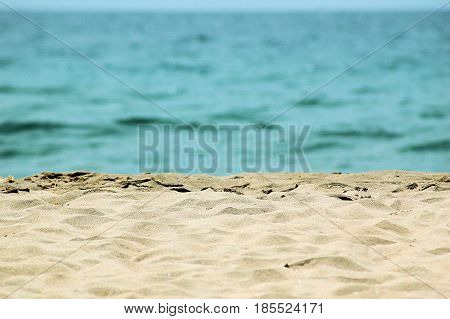 Sandy beach from close by against a blue green sea
