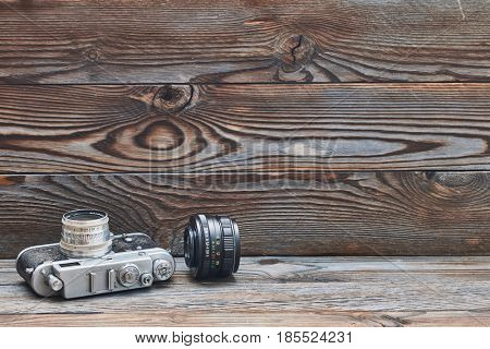 Vintage old retro 35mm rangefinder camera and lens on wooden background with copy space