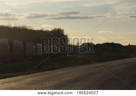 Traffic Jam of Heavy Trucks at Sunset - wide angle, horizontal