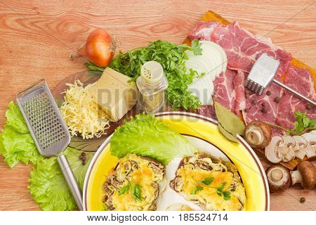Fragment of the dish with pork chops baked with onion mushrooms and cheese on the background of the ingredients and several kitchen utensils for preparation of chops on a wooden surface