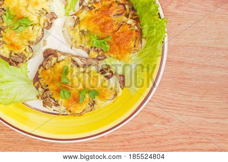 Fragment of the dish with several pork chops baked with onion mushrooms and cheese and decorated with parsley and lettuce leaves on a wooden surface