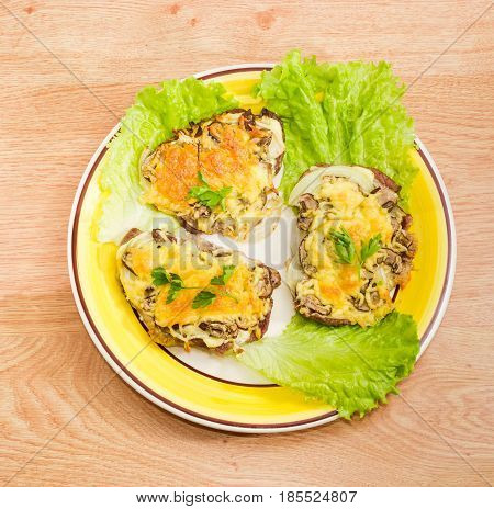Top view of three pork chops baked with onion mushrooms and cheese and decorated with twigs of the parsley and lettuce leaves on the yellow and white dish on a wooden surface