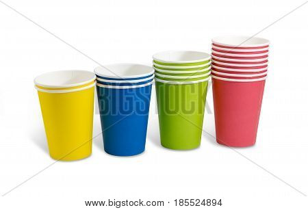 Row of the piles of the disposable paper cups in red green blue and yellow colors on a light background