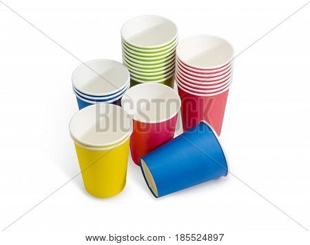 Piles of the disposable paper cups and separate cups in red green blue and yellow colors on a light background