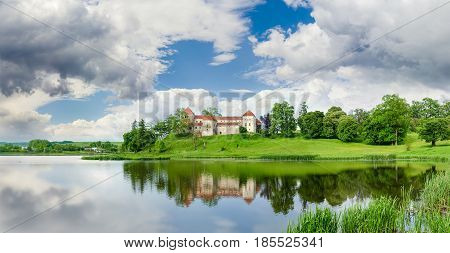Svirzh Castle built in the 15th century on the lake bank after spring thunderstorm in Lviv region Ukraine
