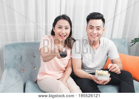 Happy Young Couple In Livingroom Sitting On Couch Watching Movie