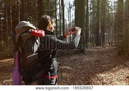 Hiker taking photographs on her hike through the woods. Memory collection active lifestyle mobile phone dependency concept.