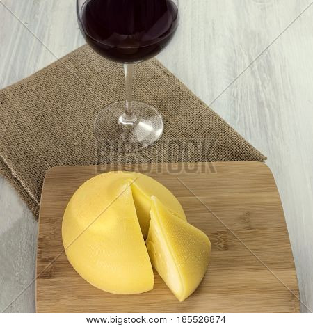 A square photo of tetilla, a traditional Spanish soft cow milk cheese, with a slice cut off, and a glass of red wine, on a wooden board with a place for text