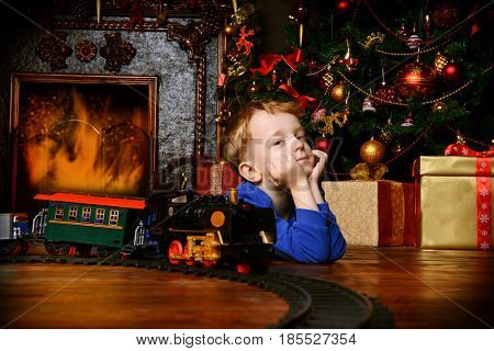 Cute little boy playing with a toy railway near the Christmas tree and fireplace. Christmas night. Christmas decoration.