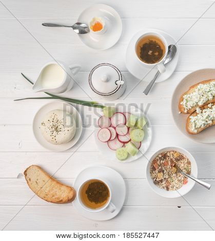 Delicious filling breakfast with salad, cheese and oatmeal, poached egg and herbal tea, topview