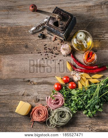 Old pepper mill and scattered pepper, rustic oil bottle, pasta and different herbs, topview