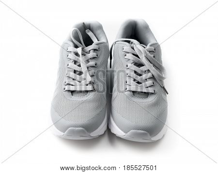 Gray cozy running shoes sitting on white wood, long shoelaces tied in, white soles