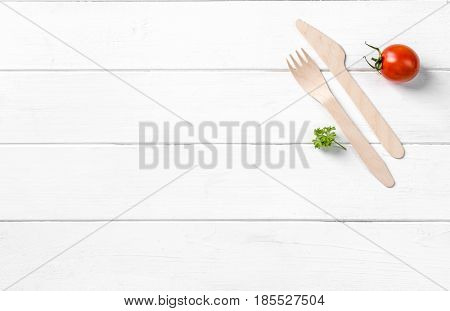 Organic food, wooden knife and fork and a tomato nearby, text space left