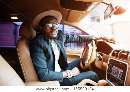 Stylish Black Man Sitting Behind The Wheel Of Luxury Car. Rich African American Businessman.