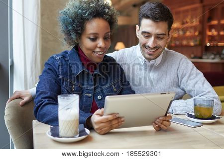 Portrait Of Joyful Smiling Interracial Couple In Cafe, Female Wearing Denim Jacket Is Holding Tablet