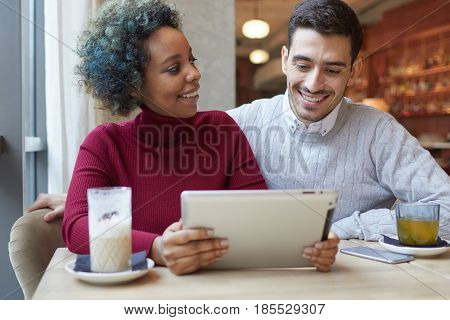 Beautiful African American Girl And Caucasian Guy Staying In Nice Cafe With Coffee And Tea, Watching