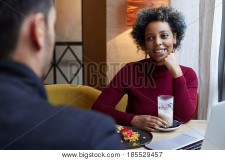 Indoor Photo Of Smiling Young Dark-skinned Woman Drinking Coffee In Cafe And Having Dessert With Lap