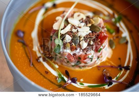 food, new nordic cuisine, culinary and cooking concept - close up of vegetable pumpkin-ginger soup with goat cheese and tomato salad with yogurt in bowl
