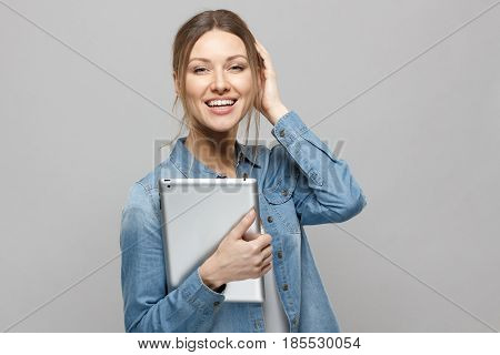 Indoor Shot Of Cute European Woman Posing Isolated On Gray Background With Tablet Pc In Her Hands, L