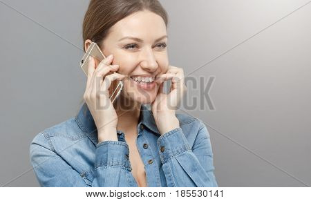 Picture Of Good-looking Girl Dressed In Denim Shirt Turned Right, Isolated On Gray Background Holdin