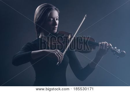Young beautiful woman playing the flute on black background