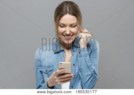Indoor Picture Of Joyful Attractive Girl Isolated On Grey Background Showing Strong Positive Emotion