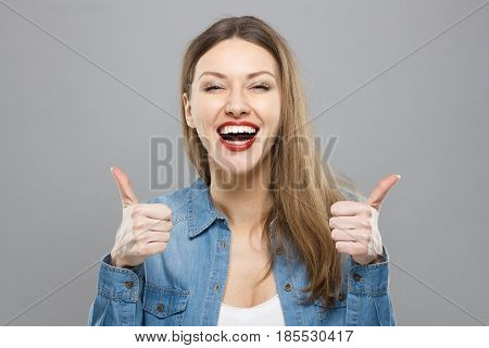 Closeup Of Young Optimistic Female Isolated On Grey Background Showing Thumps Up With Positive Emoti
