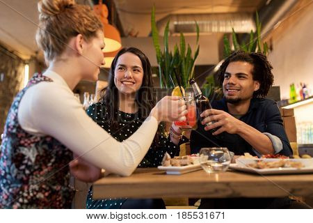leisure, celebration, party, people and holidays concept - happy friends clinking drinks at bar or cafe