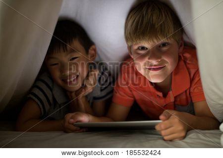 Portrait of siblings under bed sheet using digital tablet on bed in bedroom