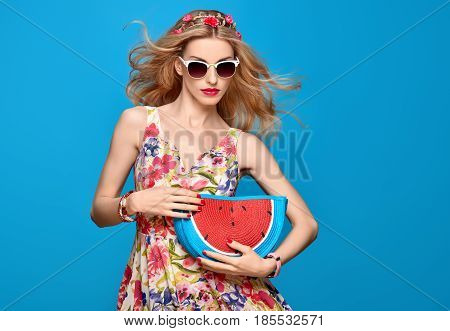 Fashion Beauty woman in Summer Outfit. Sensual Sexy Blond Model in fashion pose. Trendy Floral summer Dress, Glamour Clutch, Stylish wavy hairstyle, fashion Hairband. Playful Romantic summer Girl