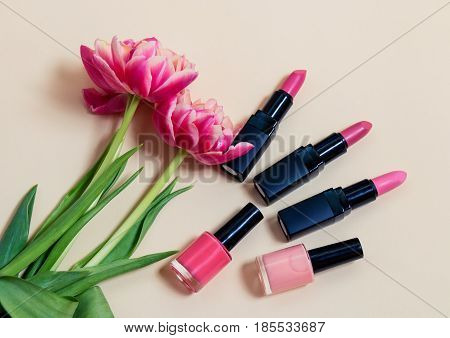 Decorative cosmetics and tulips on beige background