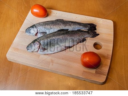 Fresh trout with tomatoes on wooden cutting board