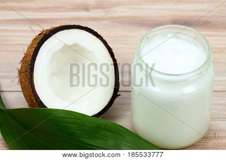 Organic coconut oil in the glass jar. Fresh coconut cut in half and leaf for decoration
