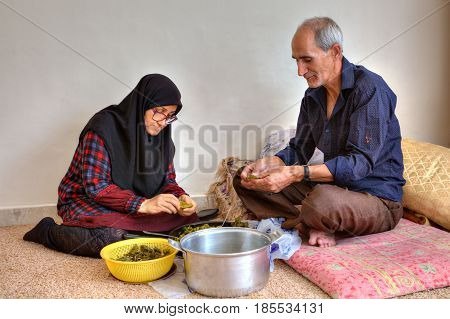 Bandar Abbas Hormozgan Province Iran - 15 april 2017: An elderly Islamic couple is preparing a dish of persian cuisine dolmeh sitting on the carpet at home.